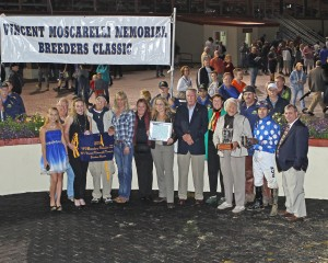 Trainer Tim Grams, jockey Oscar Flores, and friends celebrate win by Runnin'toluvya in the WV Vincent Moscarelli Memorial Breeders Classic. Photo by Coady Photography.
